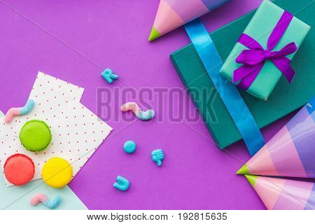 Birthday wrapped gifts and party hats on purple background top view copyspace.