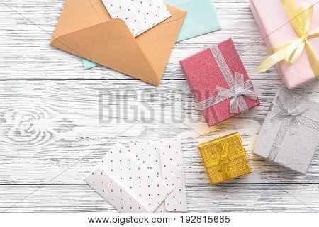 Birthday greeting cards and wrapped gifts on grey wooden desk top view copyspace.
