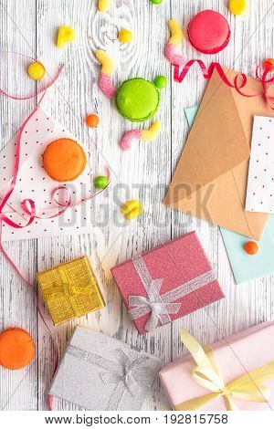 Birthday concept with wrapped gifts, greeting cards and sweets on grey background top view.