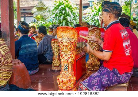 BALI, INDONESIA - APRIL 05, 2017:Unidentified people playing some musical instruments inside of a building in the beautiful temple in Ubud Bali located in Indonesia.