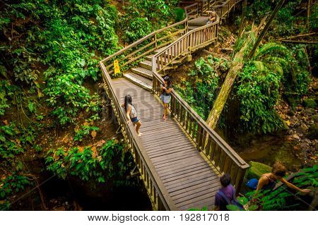 BALI, INDONESIA - MARCH 05, 2017: Unidentified people taking pictures of macaque monkeys on dragon bridge at Ubud Sacred Monkey Forest Sanctuary, a nature reserve and Hindu temple complex in Ubud, Bali, Indonesia.