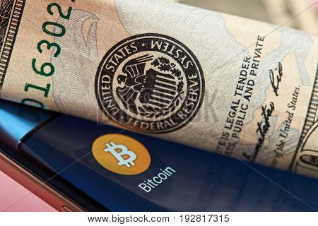 New york, USA - June 26, 2017: Bitcoin mobile application close-up against federal reserve system.Bitcoin against dollar system
