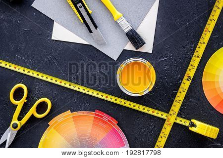 Reparing home concept. Paint and tools on black stone desk background top view copyspace.