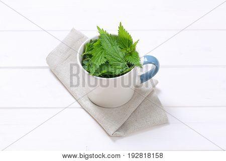 mug of fresh nettle leaves on beige place mat