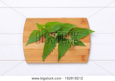 fresh nettle leaves on wooden cutting board
