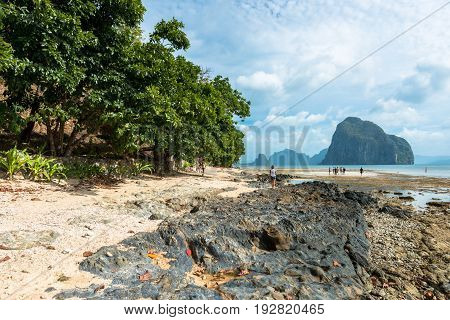 EL NIDO, PALAWAN, PHILIPPINES - MARCH 29, 2017: People enjoying Las Cabanas Beach. Trees rocks and sand compose the scene
