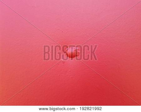 sheet of metal with rivets painted over with red paint