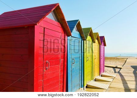 closeup of some colorful beach huts of different colors in a lonely beach, with the ocean in the background