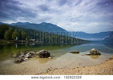 Cold mountain lake with a stones in front and fog above during with cloudy sky, Bohijn Lake, Slovenia