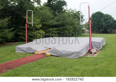A local high school pole vault pit is coverd up with a gray tarp