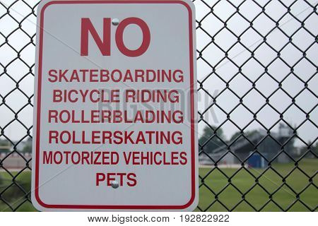 A sign on a fence that reads NO skateboarding bicycle riding rollerblading rollerskating motorized vehicles pets