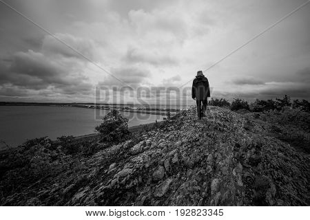 A man walks alone over a rocky path overlooking the sea, black and white