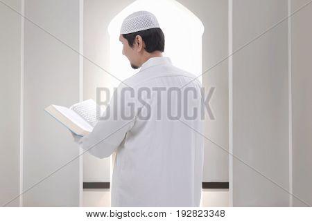 Back View Of Asian Muslim Man Reading The Koran