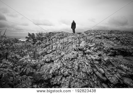 A man stands alone on a large rock at a scenic overlook, black and white