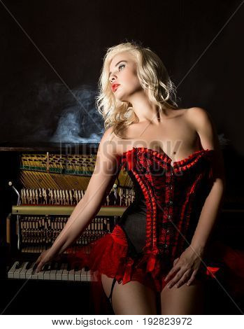 Young beautiful girl in red corset standing near the piano. Vintage style beautiful woman. Old fashioned makeup and retro finger wave hairstyle.