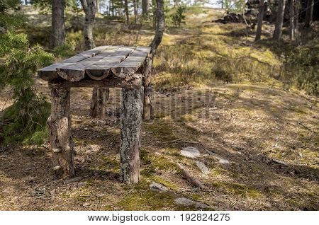 Camp on the rocky shore of the lake. Old wooden table from the pines in spring forest.