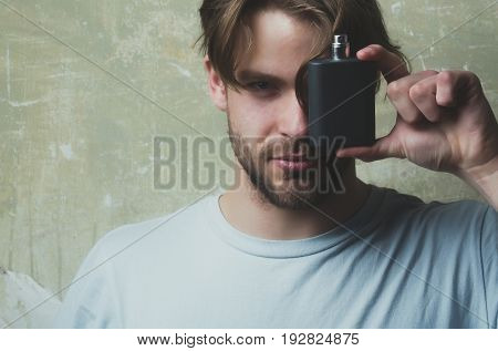 Man Covering Eye With Black Perfume Bottle
