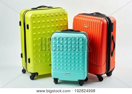 Colorful suitcases for travelling. Three colorful suitcases, white background. Summer vacation concept.
