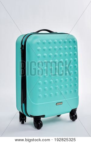 New fashionable traveler suitcase. Blue luggage on white background. Voyage with modern case.