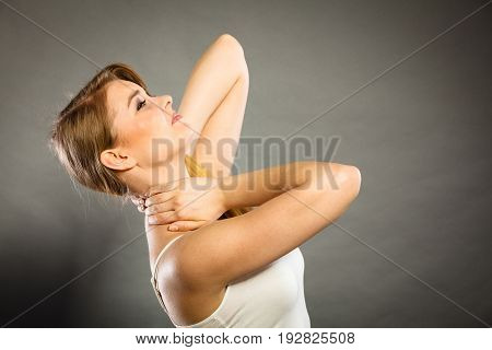Feeling exhausted back and spine disease. Woman having bad ache. Female placing hands on her neck suffering from pain