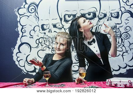 Women beautiful young successful gambling in casinos at the table with the chips and alcohol