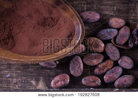 Cacao powder and raw cacao beans over rustic wooden background. Top view close up