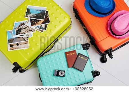Colorful suitcases for family trip. Luggage and different accessories, white background.
