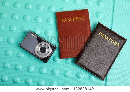 Camera, passports on textured background. Objects for tour abroad.