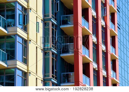 Contemporary style highrise residential building with balconies and large windows which adds to the skyline taken in an urban city neighborhood