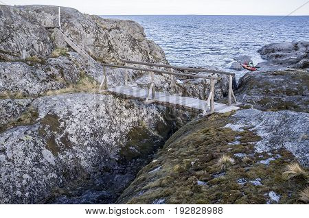 Old wooden bridge and stairs on a rocky island in the background of the lake and two kayaks parked on the beach.