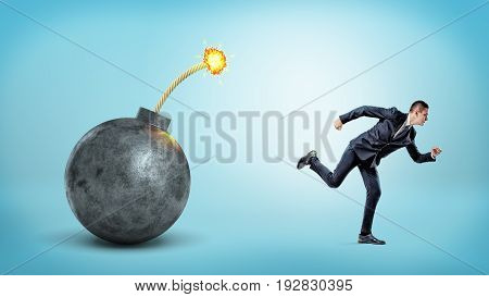 A small businessman on blue background running away from a giant bomb with a lit fuse. Save business from trouble. Market bust. Unfair competition.