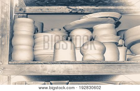 Bright pottery. Many white, not painted clay pottery standing on wooden shelves