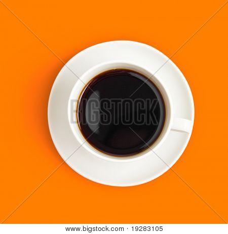 Vista superior de la taza de café negro sobre fondo naranja