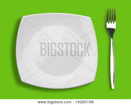 square white plate and fork on green background