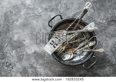 Big rustic bowl with cute designed antique dishware, spoons and forks, copyspace, topview