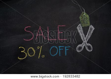 Sale 30% off. Sale and discount price sign with scissors cutting price tag drawn with chalk on blackboard