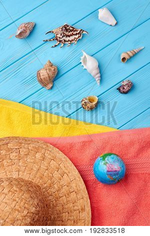 Sea shells on sea background. Hat, colored terry towels, globe. Main symbols of marine vacation.