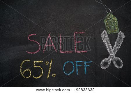 Sale 65% off. Sale and discount price sign with scissors cutting price tag drawn with chalk on blackboard