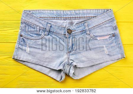 Denim shorts on yellow background. Stylish summer shorts isolated on wooden board.