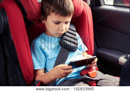 Mid shot of gloomy boy playing in phone while sitting in baby seat