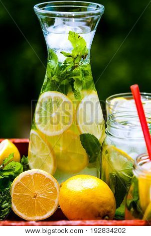 Delicious homemade lemonade in graphene and jars with mint and lemons