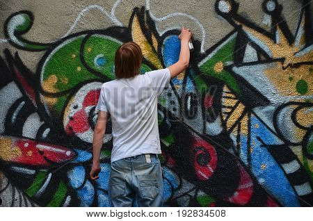 Photo In The Process Of Drawing A Graffiti Pattern On An Old Concrete Wall. Young Long-haired Blond