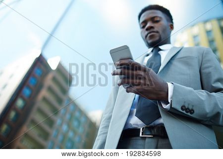 Young ceo with smartphone reading sms