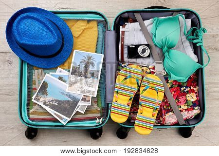 Suitcase full of beach accessories. Opened bag with summer stuff, top view.