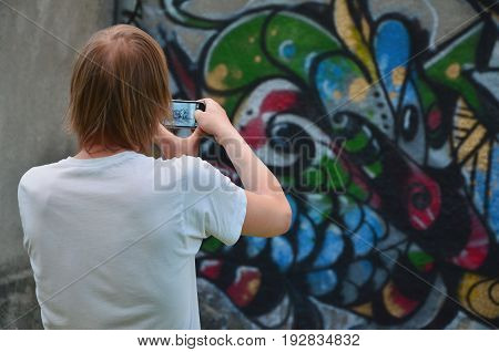 Photo In The Process Of Drawing Graffiti On An Old Concrete Wall. A Young, Long-haired Blond Guy Tak