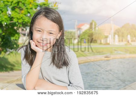 Portrait Of Little Asian Girl Smiling And Playing In The Garden. Concept Little Girl Attractive.