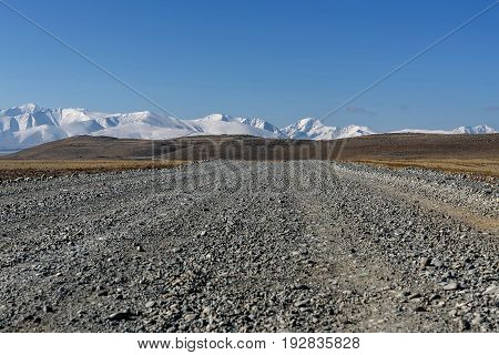 A picturesque view with a gravel road in the steppe mountains covered with snow and hills on the background of blue sky on a sunny day