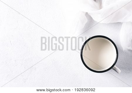 Milk In An Iron Mug On A White Concrete Background