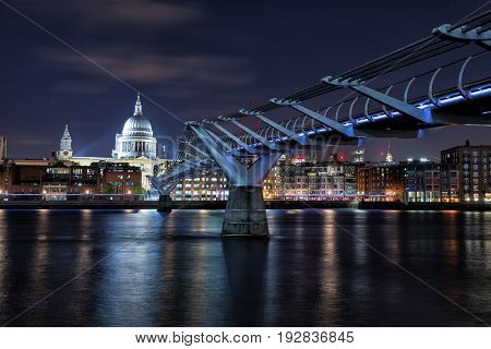 St Paul's Cathedral , the river Thames and the Millennium Bridge at night. London cityscape, showing illuminated bars and restaurants along the riverbank.