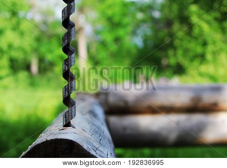 Metal spiral drill for making holes in logs when assembling a wooden frame and building a house.